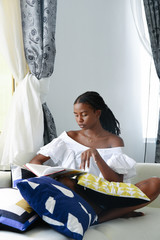 Young woman reading book while sitting cross-legged