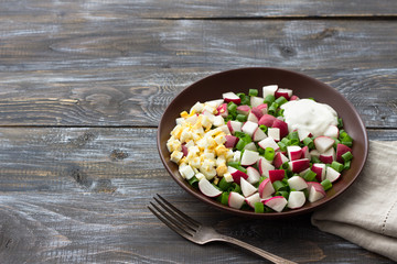 Fresh radish salad with green onions, boiled egg and sour cream on a wooden background, rustic style. Delicious homemade food