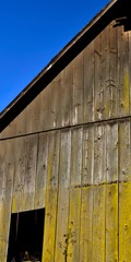 Exterior of old weathered wood barn with blue sky