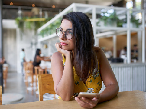 Candid lifestyle portrait of beautiful hispanic millennial woman looking out window holding cellphone in modern trendy and bright coffee shop with plants
