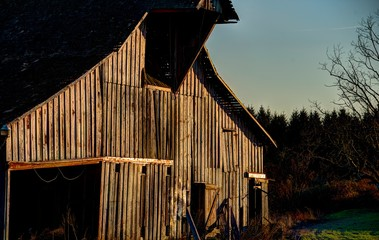Brown weathered wood barn with sunlight reflecting from tracks for doors