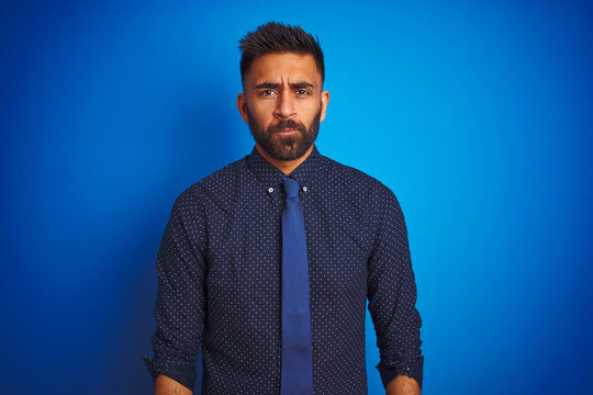 Young indian businessman wearing elegant shirt and tie standing over isolated blue background depressed and worry for distress, crying angry and afraid. Sad expression.