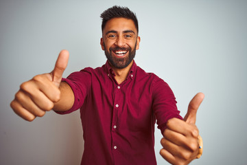 Young indian man wearing red elegant shirt standing over isolated grey background approving doing positive gesture with hand, thumbs up smiling and happy for success. Winner gesture. Wall mural