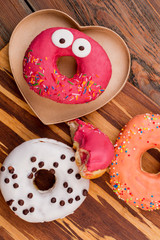 Funny donut on wooden background, top view. Still life of glazed cakes on wooden surface. Funny composition with donuts.