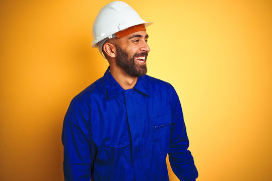 Handsome indian worker man wearing uniform and helmet over isolated yellow background looking away to side with smile on face, natural expression. Laughing confident.