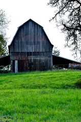 Wooden barn on hilltop with green pasture in front history,peaceful