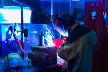 A man works on a welding machine. The welding process at the factory. Protection during welding. Welding equipment. Work with metal. Welding of metal structures. Welding production.
