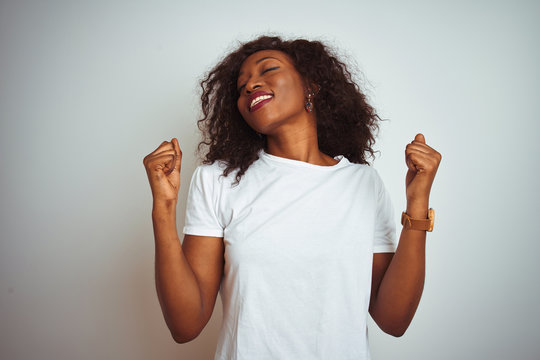 Young african american woman wearing t-shirt standing over isolated white background celebrating surprised and amazed for success with arms raised and eyes closed. Winner concept.