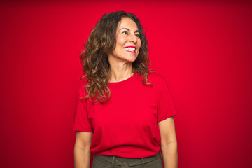 Wall Mural - Middle age senior woman with curly hair over red isolated background looking away to side with smile on face, natural expression. Laughing confident.