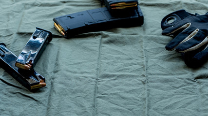 Black steel handgun pistol magazines loaded with hollow point ammunition, soft point loaded polymer AR15/M4 magazines and black and tan tactical gloves, resting on an olive drab cloth background