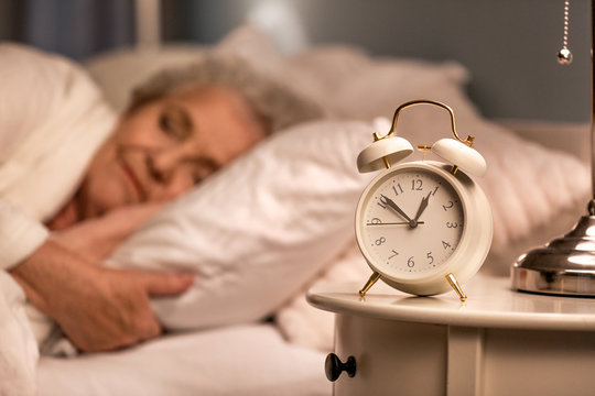 Alarm clock on table of sleeping senior woman at night
