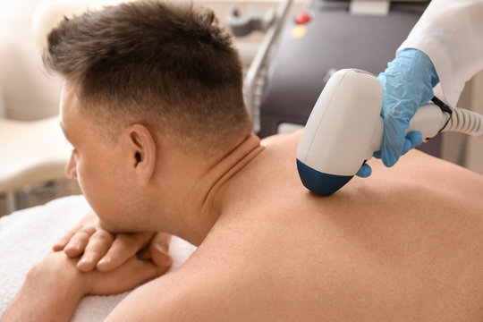 Handsome man undergoing procedure of laser hair removing in beauty salon
