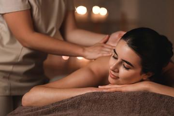 Beautiful young woman receiving massage in spa salon Fototapete