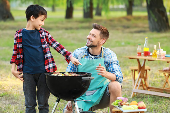 Little boy with father cooking tasty food on barbecue grill outdoors