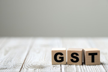 Business concept with a GST word on a wooden cube