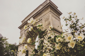 Washington Square Arch Through Blurred Flowers in New York USA