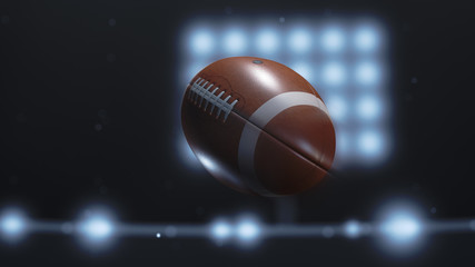 Closeup of a football flying through the air in a lit stadium at night