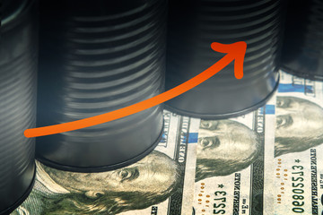 Several barrels of oil on dollars and a red arrow up - concept of higher oil prices
