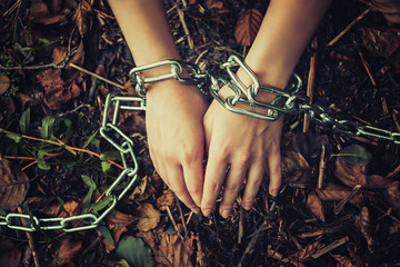 Women's hands chained in a dark forest - the concept of violence, hostage, slavery