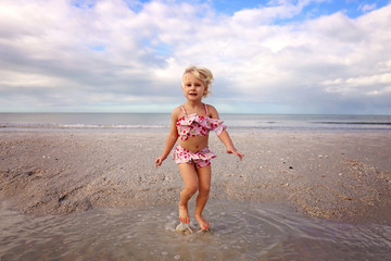Cute Little Beach Baby Jumping and Playing in the Water by the Ocean