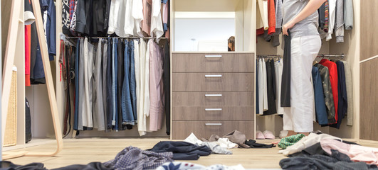 Young woman throwing clothes in walk in closet. Mess in wardrobe and dressing room