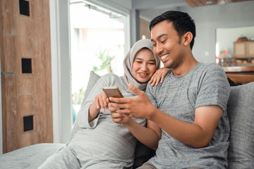 wife pregnant and husband using smartphone together at home while sitting on couch