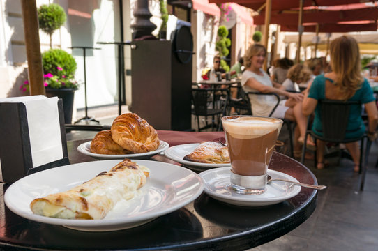 Breakfast meal with coffee and croissants served at outdoor restaurant in Italy