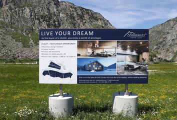A sign board advertises property on sale at the Andermatt Swiss Alps resort in Andermatt