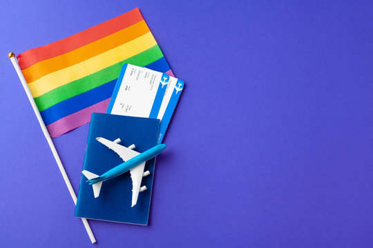 The concept of travel for gays and lesbians. Passport, toy plane and gay flag