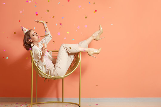 Happy woman with party whistle and glass of champagne near color wall