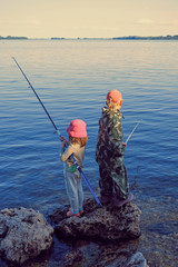 Two kids boy and girl fishing in a Volga river on a stone coast. View from the back.