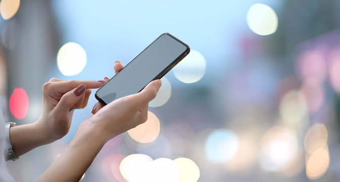 Female hands holding blank screen smartphone with blurred bokeh background..