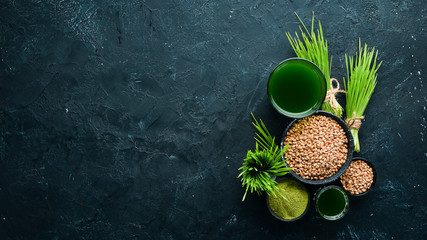 The juice from the green sprouted wheat, and wheat grains. On a black background. Micro Green. Healthy food. Top view. Free space for your text.