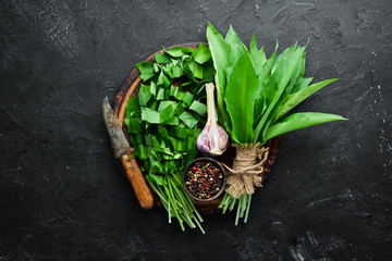 Wall Mural - Fresh wild garlic leaves on black background. Wild leek. Top view. Free space for your text.