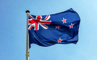New Zealand flag waving against clear blue sky