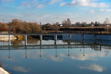 Pedestrian bridge over the dam on an autumn afternoon