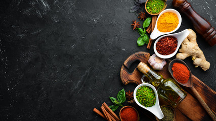 Colorful herbs and spices for cooking. Indian spices. On a black stone background. Top view.