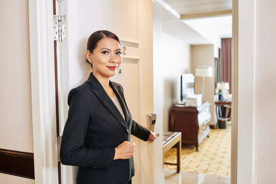 Portrait of beautiful Asian manager of the hotel in black suit standing near the door opening it and showing the hotel room