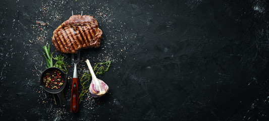 In de dag Steakhouse Grilled ribeye beef steak on the fork. At the aged table. Top view. Free space for your text.