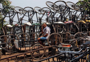 A man speaks on his mobile phone among parked trishaws in Kolkata