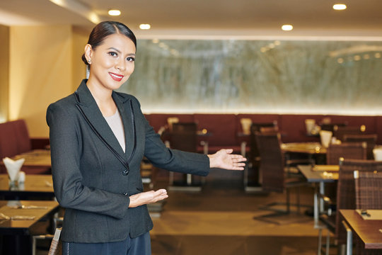 Portrait of Asian young manager in black suit showing the welcome gesture and inviting you to the new restaurant