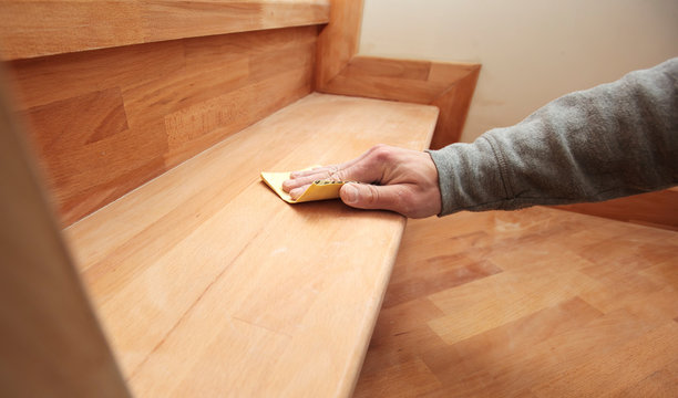 Wood grinding process by sandpaper. The young carpenter works with wood
