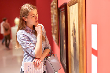 Portrait of young woman with guide looking at pictures at museum of arts