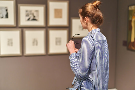 woman visitor in historical museum looking at pictures