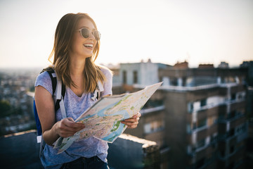Happy young woman with a city map and a backpack travelling