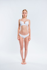 Vertical full length body size portrait of nice attractive adorable charming skinny thin sportive calm perfect healthy girl standing straight isolated over light gray background