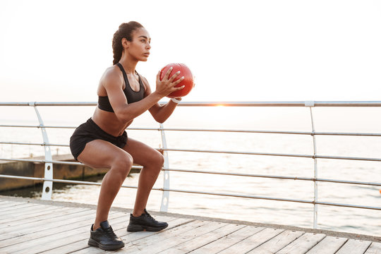 Image of young woman squatting with fitness ball while doing workout by seaside in morning