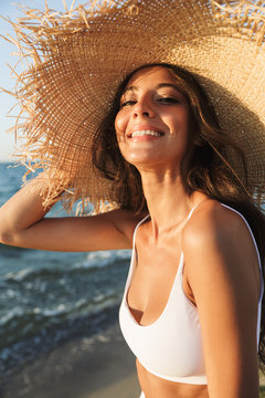 Photo of glamorous brunette woman in swimsuit and straw hat smiling and sunbathing while walking by seaside