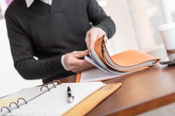 Businessman looking for document in folder - fototapety na wymiar