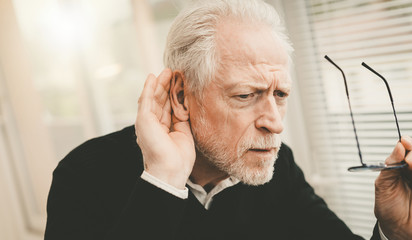 Senior man with hearing problems Fotobehang
